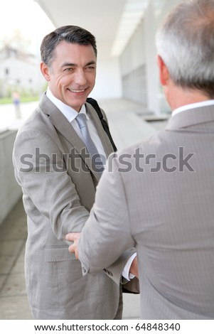 Businessmen shaking hands outside building