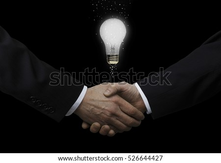 Businessmen Shaking Hands With Light Bulb