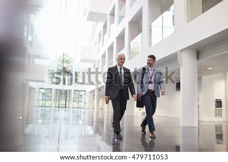 Businessmen Talking As They Walk Through Office Lobby