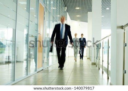 Businesspeople going along corridor inside office building