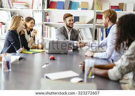 Businesspeople shaking hands in office with coworkers and staff sitting at the table with them