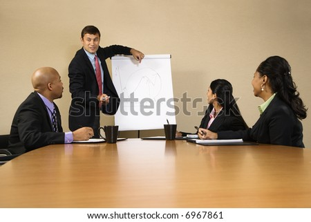 Businesspeople sitting at conference table  while businessman gives presentation.