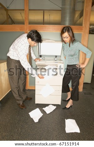 Businesspeople trying to use copy machine