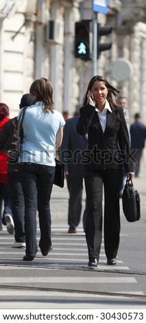 Businesswoman crossing the street while using a mobile phone.