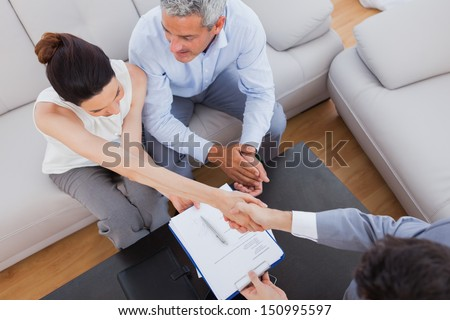 Businesswoman doing handshake with a businessman sitting on sofa at office