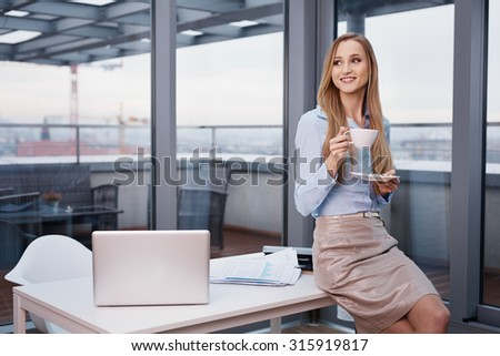 Businesswoman drinking coffee during break at office
