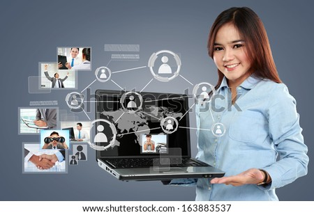 Businesswoman holding a laptop pc and surfing in the social network connection on virtual background