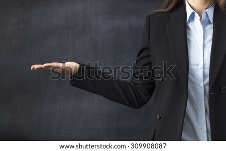 Businesswoman in formal-wear holding copy space while standing against blackboard