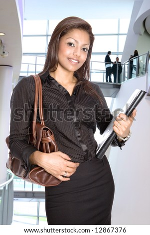 Businesswoman in modern corporate interior with team colleagues in background.