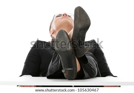 Businesswoman is siting with feet up, based on the table and looking up. Isolated on the white background.