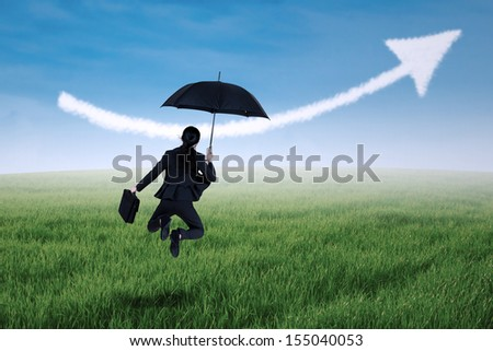 Businesswoman jumping holding umbrella in meadow and arrow up sign