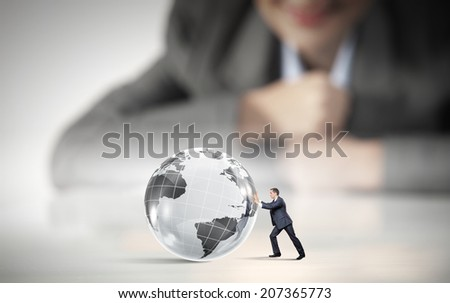 Businesswoman looking at miniature of man rolling Earth planet