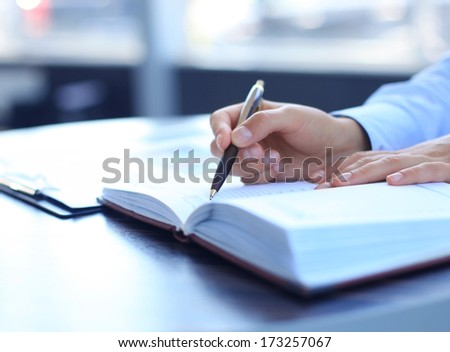 Businesswoman makes a note in notebook