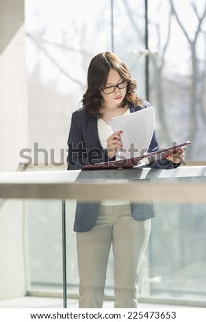 Businesswoman reviewing documents against railing in office