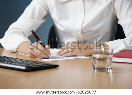 Businesswoman seating at the desk in office signing documents