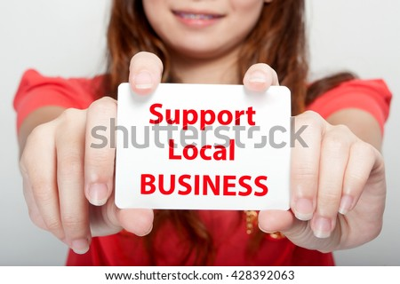 Businesswoman showing card with support local business message,