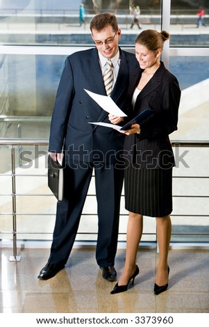 Businesswoman showing documents to her colleague in the building with glassy walls