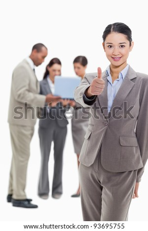 Businesswoman smiling and approving with co-workers watching a laptop in the background