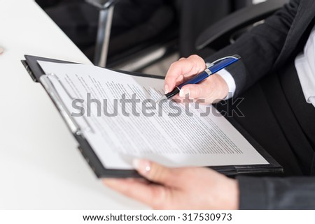 Businesswoman taking notes at office (random latin dummy text used)