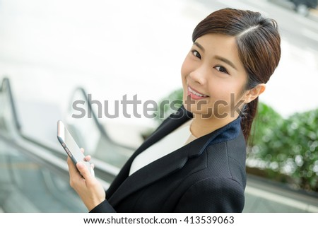 Businesswoman using her phone while going down an escalator