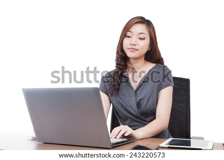 Businesswoman using laptop computer at office. Mixed race chinese / caucasian model isolated on seamless white background.