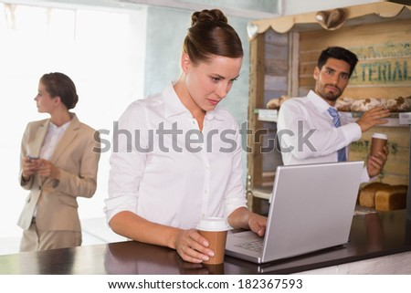 Businesswoman using laptop with colleagues behind in office cafeteria