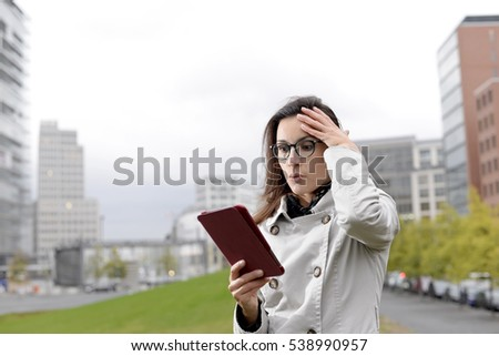 businesswoman with digital tablet reading bad news