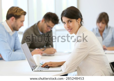 Businesswoman working on laptop, shared workspace