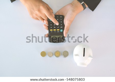 Businesswomen holding calculator with alarm clock coin and white piggy bank on blue background selective and soft focus