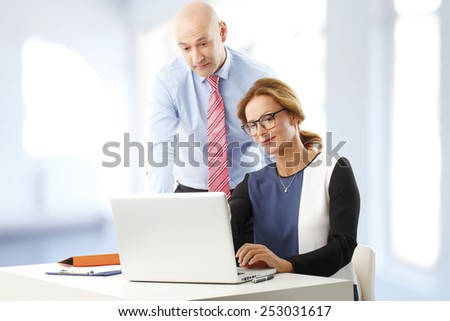 Busy business woman and businessman discussing business plan while sitting at office in front of laptop.