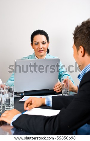 Busy business woman working on laptop in the middle of office meeting