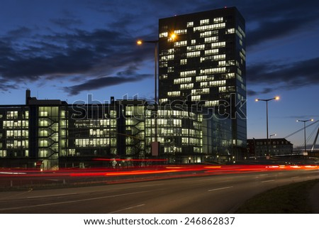 Busy road with office buildings in Munich, Germany, at night