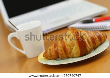 Butter croissant and coffee on office desk