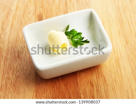 Butter curl on plate, on wooden table