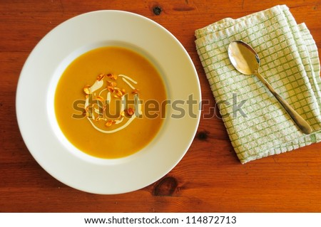 Butternut squash soup in clean white bowl on wooden table. Soup garnished with cream and spiced caramelised seeds.