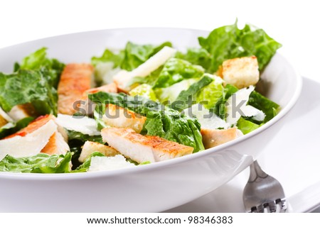 Caesar salad with chicken and greens on white background