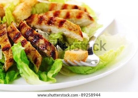 Caesar Salad with grilled chicken on white plate.