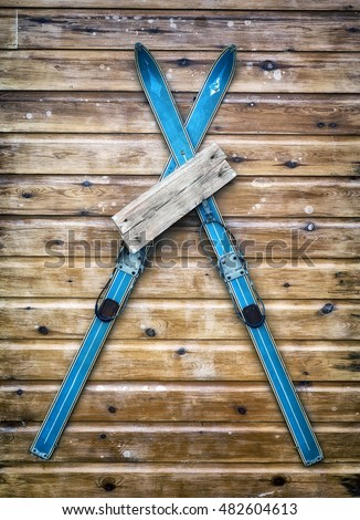 Cafe, shop or resort sign which is blank for copy space, antique wooden skis being using as part of a sign on the side of a log cabin.