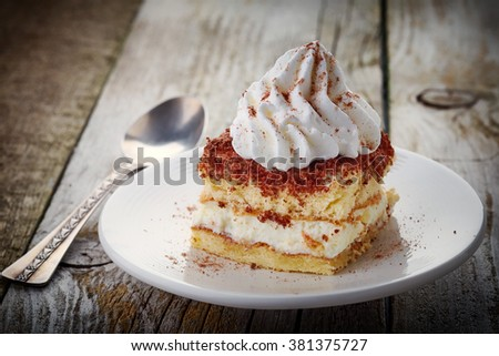 cake decorated with whipped cream on wooden table