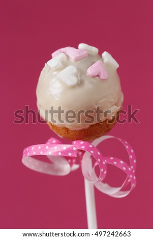 Cake pop with hearts and a pink ribbon with white polka dots on a pink background 4