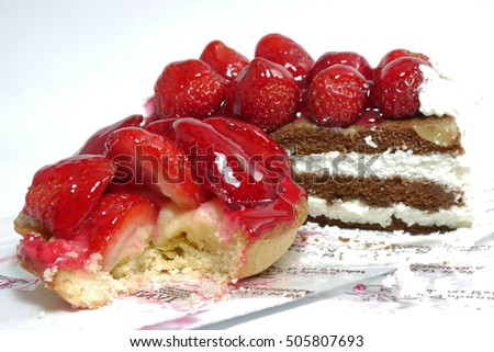 Cakes with strawberries and chocolate on a white background.
