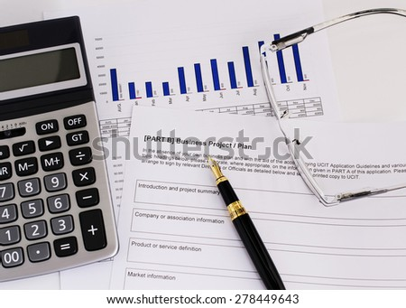 Calculator and fountain pen and eyeglasses for Business plan concept