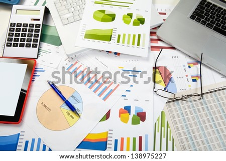Calculator, charts, notebook, business table in the office