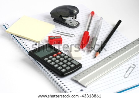 calculator pens pencil ruler and stapler on white lined notepad