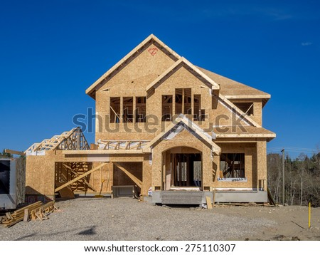 CALGARY, CANADA - APRIL 26: Suburban estate home under construction in Aspen Woods on April 26, 2015 in Calgary, Alberta. In the framing stage, this home is typical of upscale Calgary suburbs.