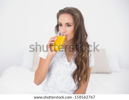 Calm attractive brunette drinking a glass of orange juice in bright bedroom