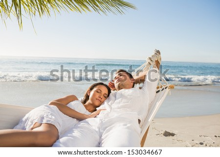 Calm couple napping in a hammock at the beach