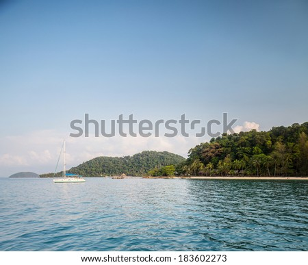 Calm lagoon with sandy beach and anchored sail boat