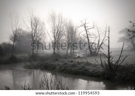 calm river running through misty fields