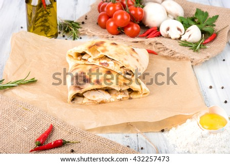calzone with chicken , mushrooms , tomatoes and mozzarella